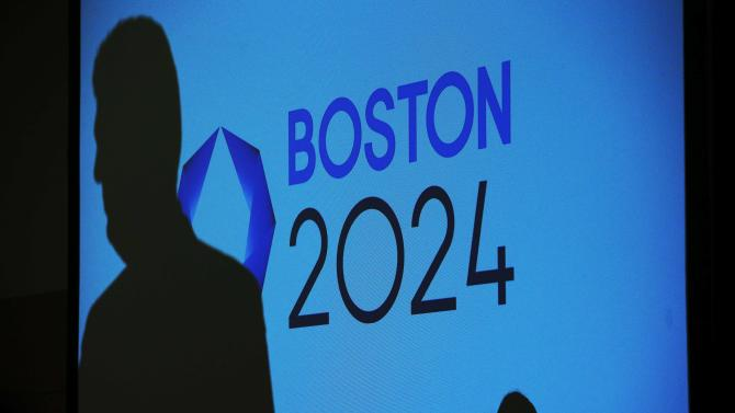 File photo of people casting shadows on a video display before a news conference explaining Boston's bid to host the 2024 Summer Olympics in Boston