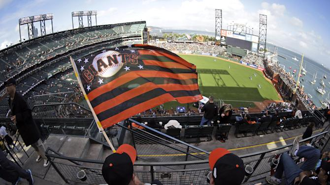 San Francisco Giants fans Jason Strother, left, and Jeremy Strother, wave their Giants flag before Game 4 of baseball's World Series between the Kansas City Royals and the San Francisco Giants on Saturday, Oct. 25, 2014, in San Francisco. (AP Photo/Charlie Riedel)