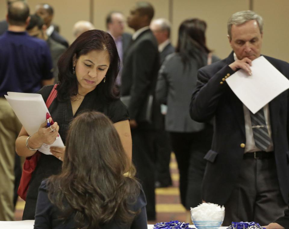 In this May 29, 2013 photo, job seeker Anu Vatal of Chicago, speaks with Patrice Tosi of BluePay, seated, during a career fair in Rolling Meadows, Ill. The government issues the May jobs report on Friday, June 7, 2013. (AP Photo/M. Spencer Green)