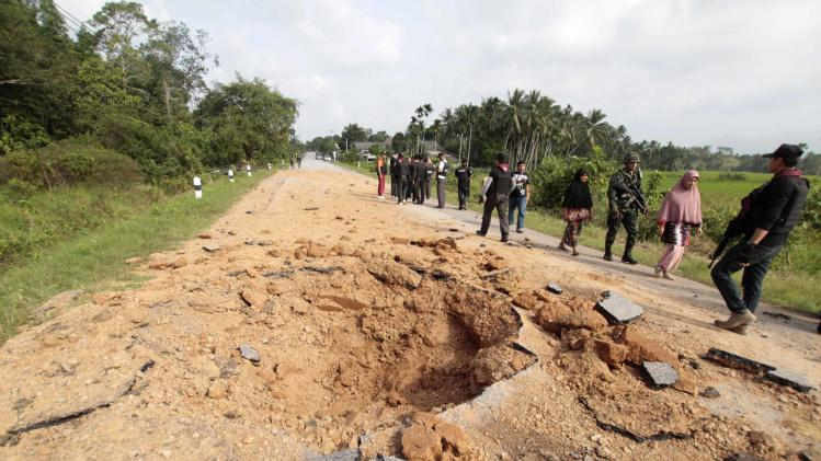 Thai security personnel and villagers walk past a bomb attack site in Pattani