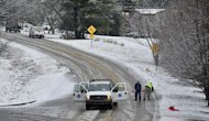 City of Huntsville workers set up road blocks on Green Mountain Road while a salt truck clears the road during a brief winter storm which brought light snow and icy roads to north Alabama Thursday, Jan. 17, 2013 in Huntsville, Ala. A winter storm made its way across the Southeast on Thursday, dumping snow in states recovering from days of rain, playing a role in at least one fatality, and leaving thousands without power. (AP Photo/AL.com, Eric Schultz)