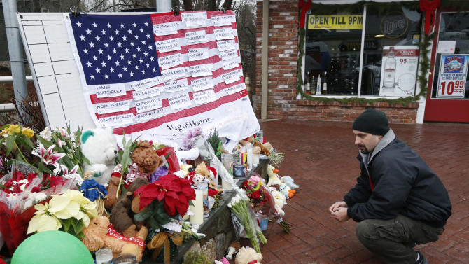Mark Sorrentino, of Naugatuck, Conn., pays respects near a U.S. flag donning the names of victims on a makeshift memorial in the Sandy Hook village of Newtown, Conn., as the town mourns victims killed in a school shooting, Monday, Dec. 17, 2012. Authorities say a gunman killed his mother at their home and then opened fire inside the Sandy Hook Elementary School in Newtown, killing 26 people, including 20 children, before taking his own life, on Friday. (AP Photo/Julio Cortez)