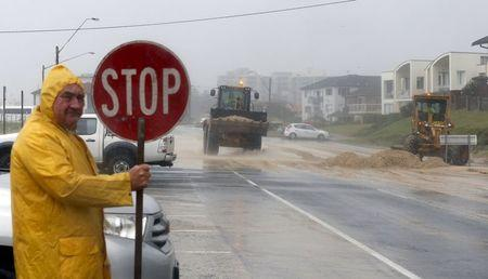 Loaders move tons of sand pushed by strong winds and rain onto a coastal road in Sydney's beachside suburb of Cronulla