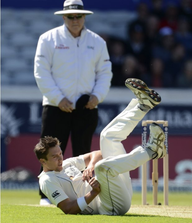 New Zealand's Boult falls over after bowling a ball as umpire Davis watches during the second test cricket match against England in Leeds
