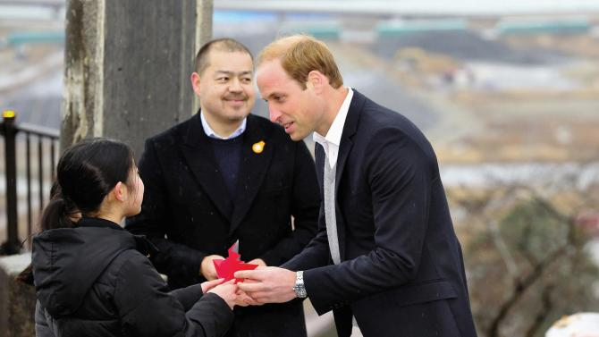 Britain's Prince William, Duke of Cambridge, is presented a paper crane from local children as he visits at Hiyoriyama Park in Ishinomaki, Miyagi Prefecture