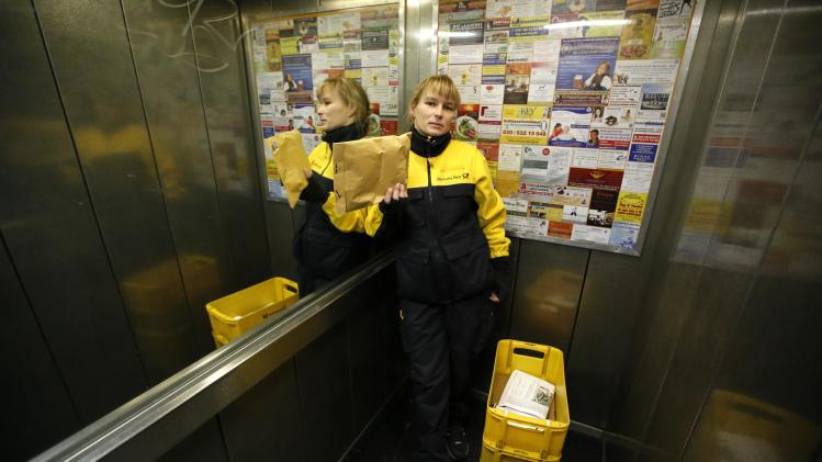 Postwoman Standke of Deutsche Post waits inside an elevator during her delivery tour in Berlin