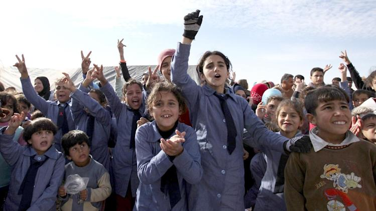 "Syrian refugee students wave to welcome United Nations Secretary-General Ban Ki-moon, unseen, to Zaatari Syrian refugee camp, in Mafraq, Jordan, near the Syrian border, Saturday, Dec. 7, 2012. U.N. Secretary-General Ban Ki-Moon on Friday called on the Syrian government to ""stop the violence in the name of humanity"", during a visit to the Zaatari refugee camp in Jordan, close to the Syrian border. (AP Photo/Mohammad Hannon)"