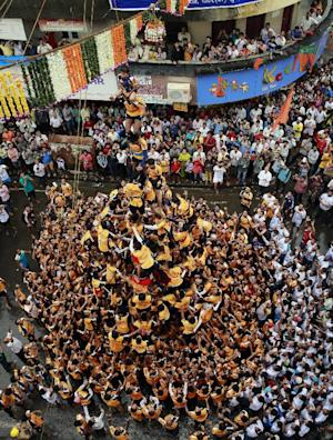 """Indian youth form a human pyramid to break the """"Dahi handi,"""" an earthen pot filled with curd, an integral part of celebrations to mark Janmashtami in Mumbai, India, Monday, Aug. 18, 2014. Janmashtami is the festival that marks the birth of Hindu god Krishna. (AP Photo/Rafiq Maqbool)"""