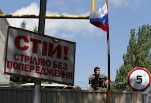 A pro-Russian fighter sits under a Russian flag as…