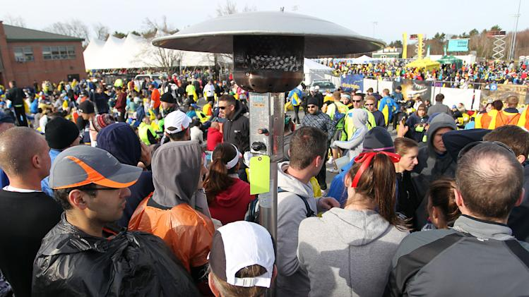 Runners gather around a portable heater in the athletes village prior to the start of the 117th running of the Boston Marathon, in Hopkinton, Mass., Monday, April 15, 2013. (AP Photo/Stew Milne)