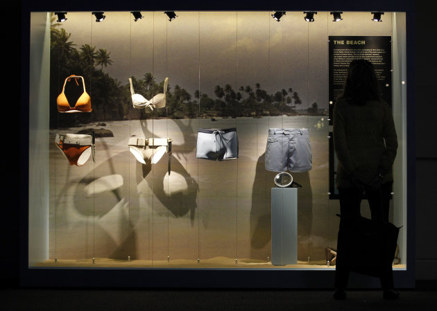 A visitor looks at a display showing, from left, an orange bikini worn by Jinx, by actress Halle Berry, in the film 'Die Another Day', a white bikini worn by Honey Ryder by actress Ursula Andress in film Dr No, James Bond's, actor Daniel Craig swimming trunk in film 'Casino Royale' and James Bond's, actor Sean Connery beach shorts in the film 'Thunderball' in the exhibition 'Designing 007 - Fifty Years of Bond Style' at the Barbican centre in London, Thursday, July 5, 2012. (AP Photo/Sang Tan)