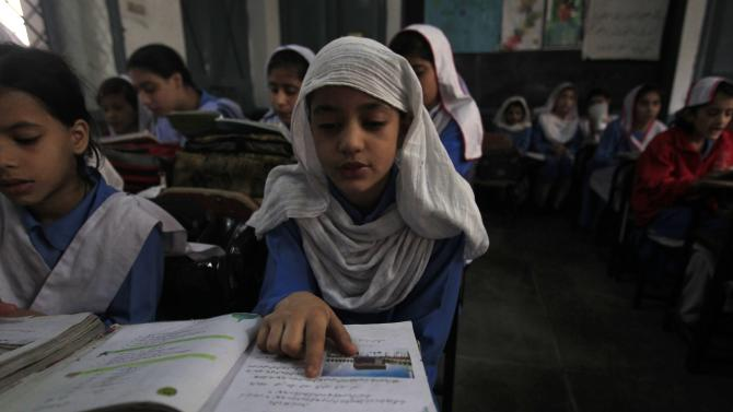 A girl reads a book while attending her daily class with others at a government school in Peshawar