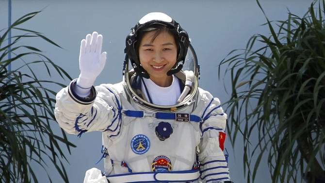 China's first female astronaut Liu Yang, waves during a sending off ceremony before she departs for the Shenzhou 9 spacecraft rocket launch pad at the Jiuquan Satellite Launch Center in Jiuquan, China, Saturday, June 16, 2012. China will send its first woman and two other astronauts into space Saturday to work on a temporary space station for about a week, in a key step toward becoming only the third nation to set up a permanent base in orbit.(AP Photo/Ng Han Guan)