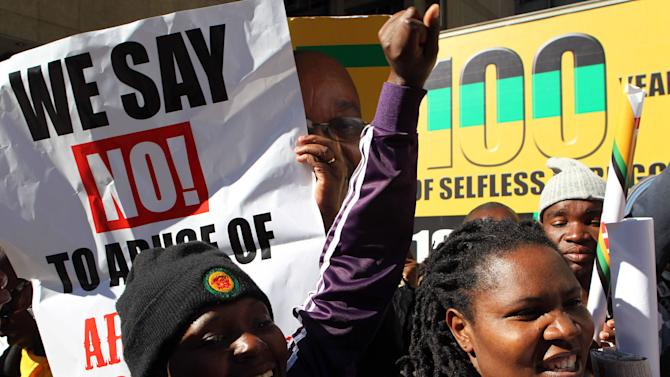 Ruling party African National Congress (ANC) supporters holding posters reacts outside the South Gauteng High Court in Johannesburg, South Africa on Thursday May 24, 2012. President Jacob Zuma is asking the High Court to issue an order that display of the now-defaced painting violates his constitutional right to dignity. The gallery and the artist counter that freedom of expression, also protected by the constitution, is at stake. (AP Photo/Themba Hadebe)