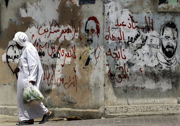 "A man walks past graffiti on a wall with Ibrahim Sharif, the Sunni leader of the liberal al-Wa'ad opposition party, left, and Arabic that reads, ""Ibrahim Sharif, no difference between Sunni and Shia, you are a jailed hero,"" and Shiite political leader Abdul Wahab Hussein, right, with Arabic that reads, ""teacher Abdul Wahab, master of the revolution,"" in the western village of Malkiya, Bahrain, Sunday, Aug. 12, 2012. The jailed opposition leaders are scheduled to hear verdicts this week in their appeals of lengthy military court sentences relating to the Spring 2011 pro-democracy uprising. (AP Photo/Hasan Jamali)"