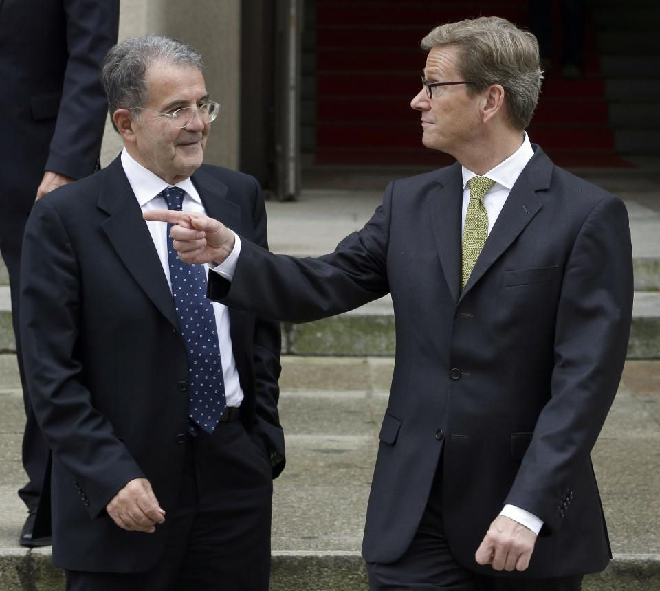 German Foreign Minister Guido Westerwelle, right, points as he and the President of the African Union-UN peacekeeping panel, Romano Prodi, left, pose in front of the Foreign Office after a press conference as part of a meeting in Berlin, Germany, Tuesday, Oct. 23, 2012. (AP Photo/Michael Sohn)