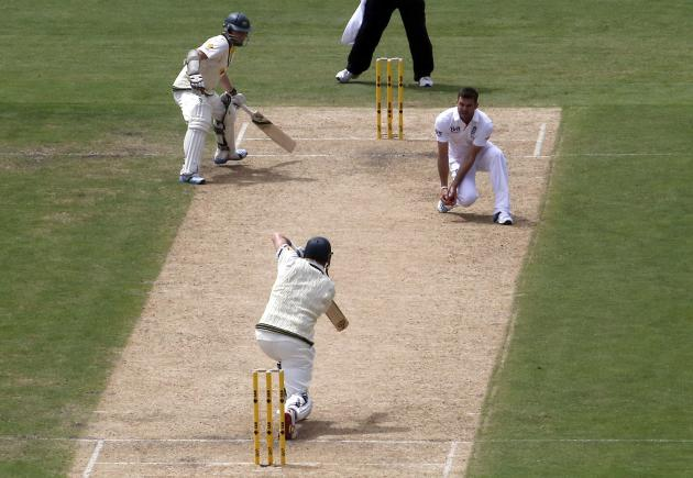 England's James Anderson takes a catch to dismiss Australia's Shane Watson for 51 runs, as Chris Rogers looks on, during the first day's play in the second Ashes cricket test at the Adelai