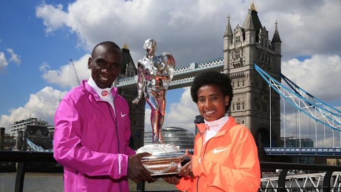 Kenya's Eliud Kipchoge, left, and Ethiopia's Tifgist Tufa  winners of the women's and men's London Marathon pose with a  trophy at the winner's photocall  in  London Monday April 27, 2015. (Nick Potts/PA, via AP) UNITED KINGDOM OUT