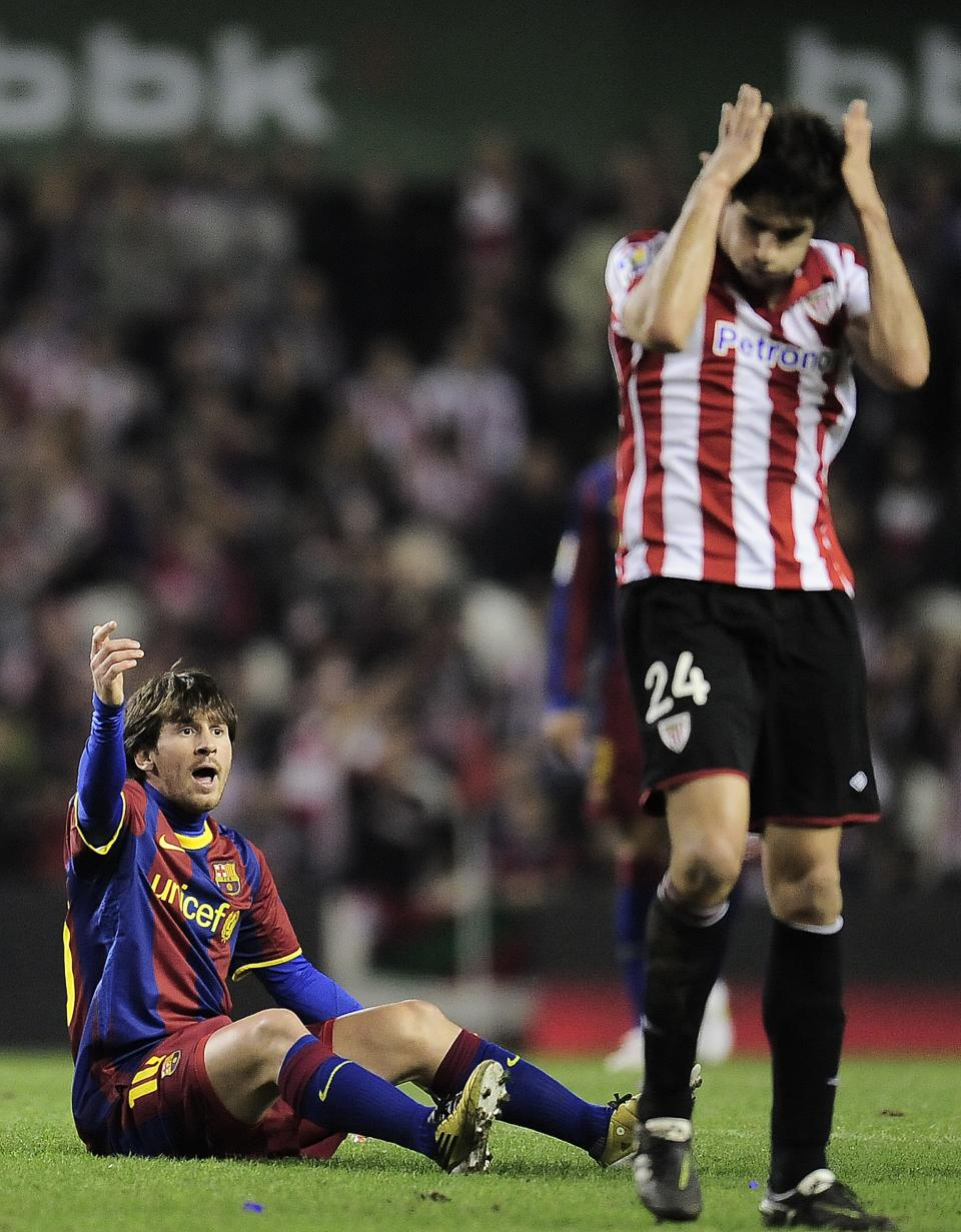Barcelona's Lionel Messi from Argentina, left, reacts,  as Athletic Bilbao's Javier Martinez, gestures during their Spanish second-leg Copa del Rey soccer match at San Mames stadium in Bilbao northern Spain Wednesday Jan.5, 2011. (AP Photo/Alvaro Barrientos)