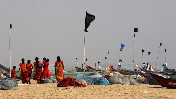 Onlookers standing on the Marina Beach watch the waves of the Bay of Bengal during a ceremony to commemorate the 10th anniversary of the 2004 Tsunami in Chennai, India, Friday, Dec. 26, 2014. Crying onlookers took part in beachside memorials and religious services across Asia on Friday to mark the 10th anniversary of the Indian Ocean tsunami that left more than a quarter million people dead in one of modern history's worst natural disasters. (AP Photo/Arun Sankar K)
