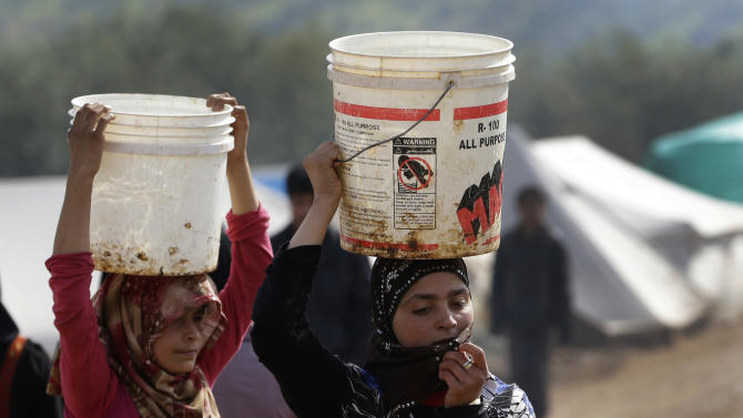 In this Tuesday, Feb. 19, 2013 photo, Syrian refugee girls carry over their heads buckets of water as they walk at Atmeh refugee camp, in the northern Syrian province of Idlib, Syria. This rebel-controlled camp only yards from the border with Turkey houses some 16,000 people displaced by the civil war. But the U.N. and other major aid agencies best equipped to handle such a large-scale relief agency cannot reach them because they are inside Syria. That leaves the job to smaller organizations who can only provide a fraction of the needs. (AP Photo/Hussein Malla)