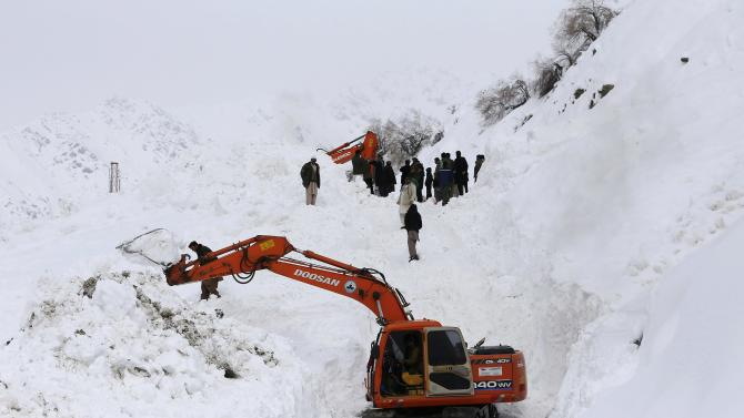 Afghan survivors of an avalanche gather as excavators clear snow from a road near Abdullah Khil village in the Dara district of Panjshir province
