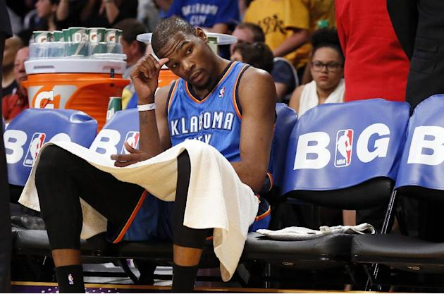 Oklahoma City Thunder forward Kevin Durant sits down on the bench as his team trails the Los Angeles Lakers after the third quarter of an NBA basketball game in Los Angeles, Sunday, March 9, 2014. The