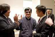 Chinese dissident Chen Guangcheng (C) shakes hands with Gary Locke (R), US ambassador to China in Beijing. Chen&#39;s flight came despite round-the-clock surveillance at his house in Shandong, where he has alleged that he and his family suffered severe beatings after he ended a four-year jail term in 2010