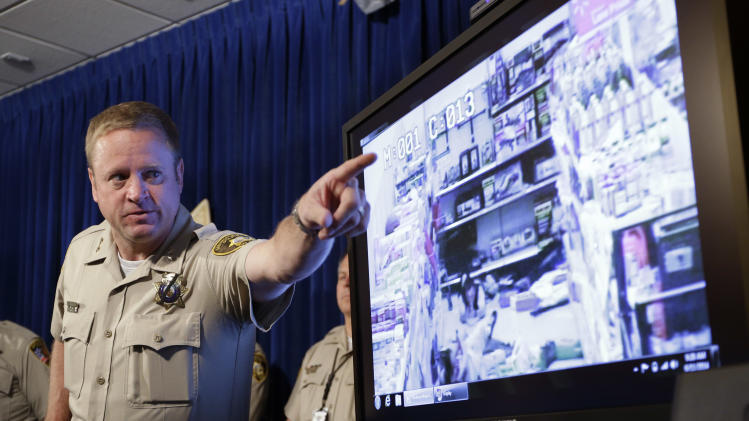 Las Vegas Metropolitan Police Department Assistant Sheriff Kevin McMahill points to a surveillance video during a news conference on Wednesday, June 11, 2014 in Las Vegas. The video shows suspects Jerad Miller and Amanda Miller in a Wal-Mart during a shootout with police. The couple shot and killed two officers who were on their lunch break at a pizza parlor, on June 8, then went to a nearby Wal-Mart, where Amanda Miller killed a shopper who confronted her husband before police arrived. After a gun battle inside the store, Amanda Miller fatally shot her husband and then herself, police said. (AP Photo/John Locher)