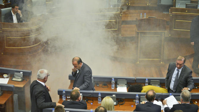 Opposition lawmakers in Kosovo disrupt Parliament's session using tear gas and whistles, in capital Pristina on Thursday, Oct. 8, 2015. The opposition protested over the government's recent EU-sponsored deal with Serbia giving the country's Serb-majority areas greater powers. (AP Photo)