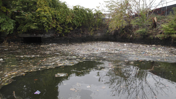 This Oct. 24, 2012 photo shows wastewater lapping the banks of Newtown Creek in New York. Just across the East River from Manhattan, within sight of the United Nations and shimmering midtown skyscrapers, tens of millions of gallons of pollution are awaiting cleanup in a neighborhood where working-class families have lived for generations and wealthier ones are moving in. Newtown Creek straddling Brooklyn and Queens is home to a federal Superfund site the size of 55 football fields. (AP Photo/Mary Altaffer)