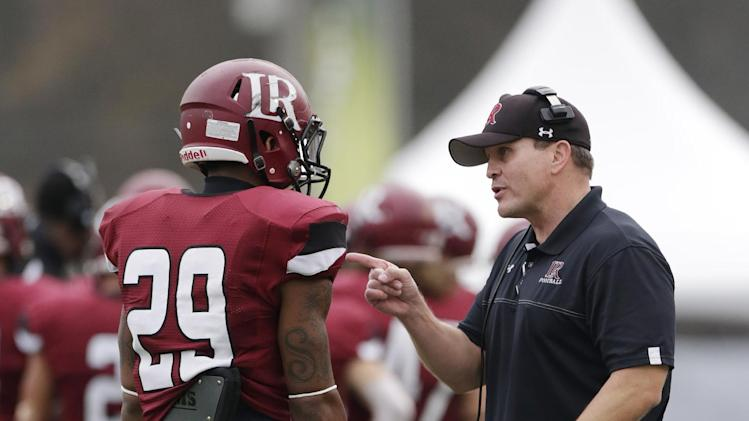 Lenoir Rhyne coach Mike Houston talks with defensive back Rodney Singleton (29) during the first half of the NCAA Division II championship college football game against NW Missouri State in Florence, Ala., Saturday, Dec. 21, 2013