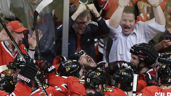 Chicago Blackhawks defenseman Brent Seabrook, center, looking up, celebrates with his teammates after scoring during the overtime in Game 7 of the NHL hockey Stanley Cup Western Conference semifinals against the Detroit Red Wings, Wednesday, May 29, 2013, in Chicago. The Blackhawks won 2-1. (AP Photo/Nam Y. Huh)