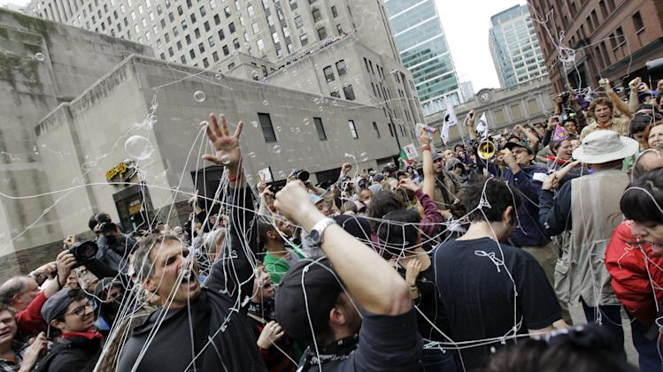 Protesters shoot silly strings and blow bubbles while demonstrating in front of Boeing corporate offices as a part of the NATO summit Monday, May 21, 2012 in Chicago. (AP Photo/Nam Y. Huh)