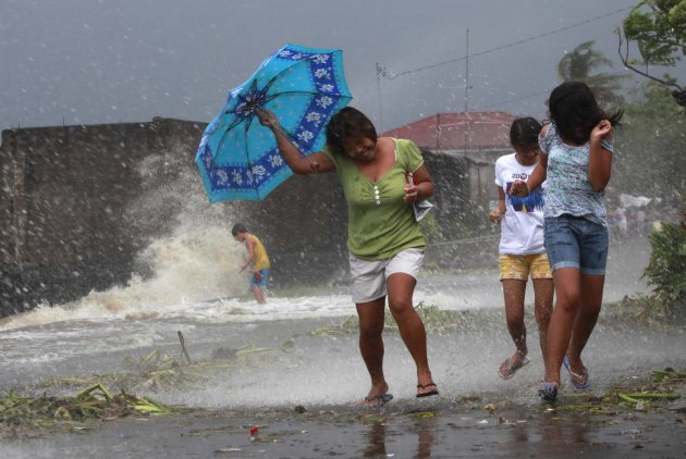 Residents walk along the coastal village while strong winds from Typhoon Haiyan battered Bayog town in Los Banos, Laguna, south of Manila November 8, 2013. Super Typhoon Haiyan, the strongest typhoon in the world this year and possibly the most powerful ever to hit land battered the central Philippines on Friday, forcing millions of people to flee to safer ground, cutting power lines and blowing apart houses. Haiyan, a category-5 super typhoon, bore down on the northern tip of Cebu Province, a popular tourist destination with the country's second-largest city, after lashing the islands of Leyte and Samar with 275 kph (170 mph) wind gusts and 5-6 meter (15-19 ft) waves. REUTERS/Charlie Saceda (PHILIPPINES - Tags: DISASTER ENVIRONMENT TPX IMAGES OF THE DAY)