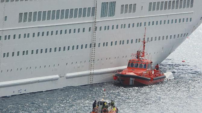 An orange rescue boat docks by a capsized lifeboat, obscured behind, from the British-operated cruise ship Thomson Majesty in Santa Cruz port of the Canary Island of La Palma, Spain, Sunday Feb. 10, 2013. A lifeboat from the Thomson Majesty fell into the sea at port in Spain's Canary Islands, killing five people and injuring three others Sunday, officials said. Rescue personnel were called to the dockside after a lifeboat with occupants had fallen overboard from a cruise ship. Spanish national broadcaster RTVE said an emergency training drill was taking place at the time of the accident. (AP Photo/Manuel Gonzalez)
