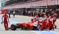 Mechanics push the car of Ferrari's Spanish driver Fernando Alonso in the pits at the Circuit de Catalunya