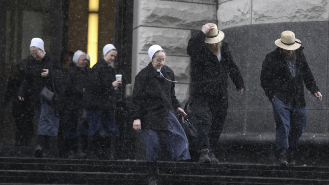 Amish men and women leave the U.S. Federal courthouse Friday, Feb. 8, 2013, in Cleveland. Sam Mullet Sr., 67, the ringleader in a series of unusual hair- and beard-cutting attacks on fellow Amish religious followers in the U.S., was sentenced Friday to 15 years in prison, and 15 family members received sentences of one year to seven years. The defendants were charged with a hate crime because prosecutors believe religious differences brought about the attacks. (AP Photo/Tony Dejak)