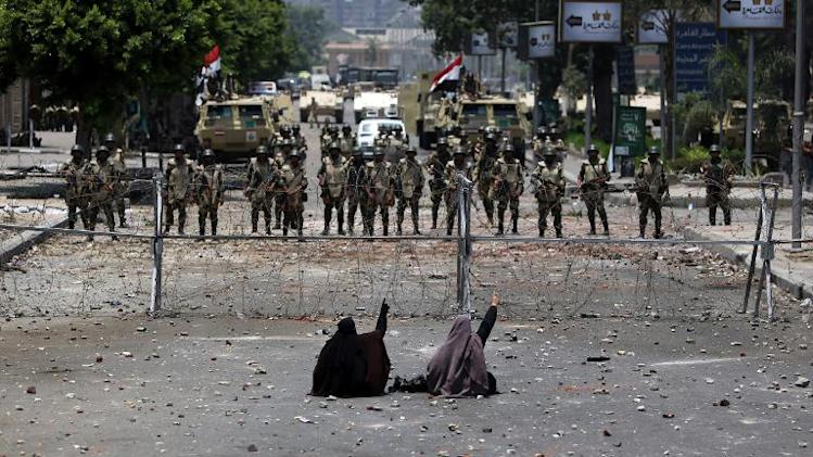 Two Egyptian women, supporters of deposed president Mohamed Morsi, sit in front police standing behind barbed wire outside the HQ of the Republican Guard in Cairo on July 8, 2013