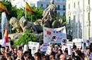 """Demonstrators hold signs as they protest in front of Cibeles fountain against the public security law """"ley mordaza"""", or """"gag law"""" in Madrid on June 30, 2015"""