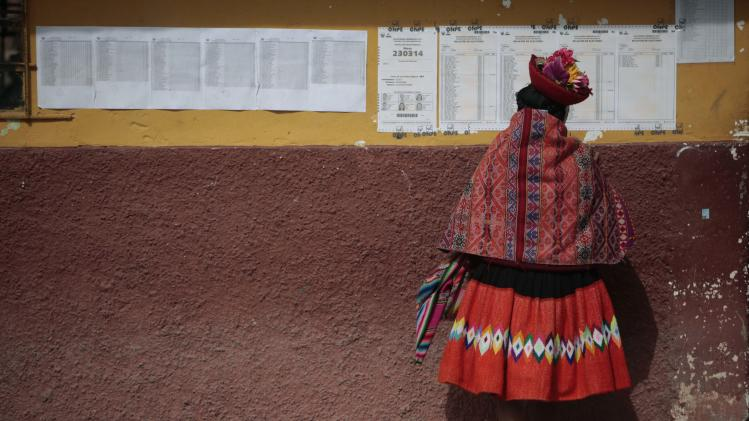 A Quechua indigenous woman looks for her voting booth number at a polling station during the presidential runoff election in Ollantaytambo village in Peru, Sunday June 5, 2011. Peruvians vote Sunday in their country's closely contested presidential race between Keiko Fujimori, daughter of jailed ex-president Alberto Fujimori and Ollanta Humala, a former military officer.  (AP Photo/Esteban Felix)