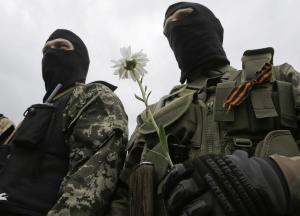 A pro-Russian fighter holds a flower after taking an…