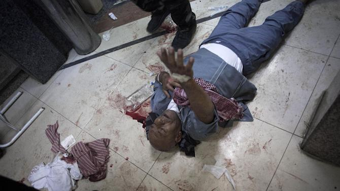 In this Wednesday, Oct. 10, 2012 photo, a wounded Syrian man begs for help while lying on the floor of Dar El Shifa hospital in Aleppo, Syria.(AP Photo/ Manu Brabo)
