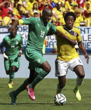 Ivory Coast's Yaya Toure, left, pushes off Colombia's Carlos Sanchez Moreno to get to the ball during the group C World Cup soccer match between Colombia and Ivory Coast at the Estadio Nacional in Brasilia, Brazil, Thursday, June 19, 2014. (AP Photo/Martin Mejia)