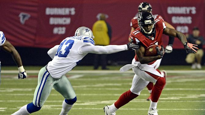 Atlanta Falcons' Julio Jones (11) tries to run past the grasp of Dallas Cowboys' Gerald Sensabaugh (43) during the second half of an NFL football game in Atlanta, Sunday, Nov. 4, 2012. Atlanta won 19-13. (AP Photo/Rich Addicks)