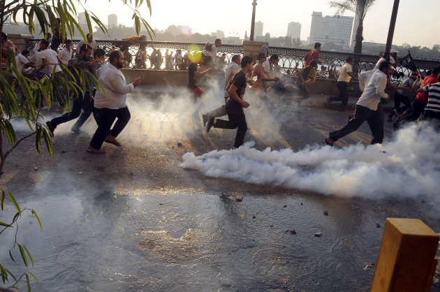 Egyptian protesters run from the site of clashes with security forces, unseen, near the U.S. embassy in Cairo, Egypt, Friday, Sept. 14, 2012, as part of widespread anger across the Muslim world about a film ridiculing Islam&#39;s Prophet Muhammad. (AP Photo/Ahmed Gomaa)