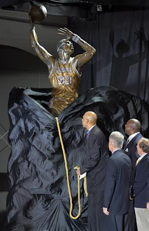 "Former Los Angeles Lakers center Kareem Abdul-Jabbar, left, unveils a statue of himself in front of Staples Center as Earvin ""Magic"" Johnson, second from right, looks on, Friday, Nov. 16, 2012, in Los Angeles. (AP Photo/Mark J. Terrill)"