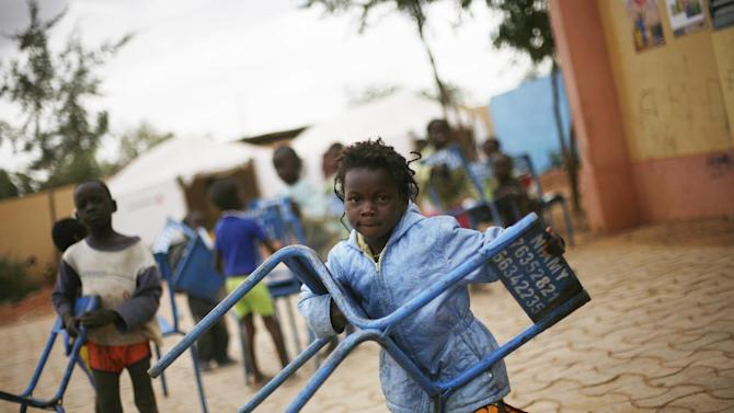 An internally displaced child carries a chair in the IDP camp sent ouside Sevare, some 620 kms (400 miles)  north of Mali's capital  Bamako Friday, Jan. 25, 2013.  One wing of Mali's Ansar Dine rebel group has split off to create its own movement, saying that they want to negotiate a solution to the crisis in Mali, in a declaration that indicates at least some of the members of the al-Qaida-linked group are searching for a way out of the extremist movement in the wake of French airstrikes. (AP Photo/Jerome Delay)