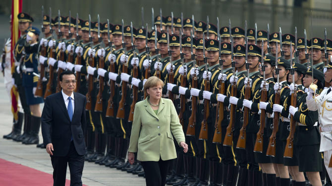 German Chancellor Angela Merkel, right, and Chinese Premier Li Keqiang, left, review an honor guard during a welcome ceremony outside the Great Hall of the People in Beijing, China Monday, July 7, 2014. (AP Photo/Andy Wong)