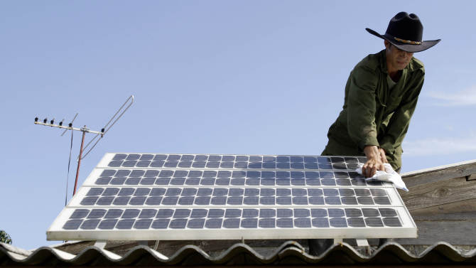 In this June 18, 2012 photo, Yusmaikel Portales cleans the solar panel on the roof of his grandfather's home in Pinar del Rio, Cuba. The Caribbean island is proud of its success in using alternative energy to bring electricity to isolated hamlets. But scientists say the island, blessed with year-around sunshine and sea breezes but plagued with chronic energy shortages, could be doing much more on the national level, and that its government is missing a golden opportunity to reduce its dependence on subsidized oil from Venezuela. (AP Photo/Franklin Reyes) (AP Photo/Franklin Reyes)